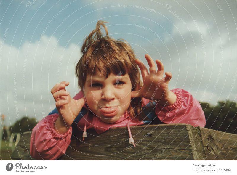 Kindheit klein frech Grimasse Mädchen Zunge rausstrecken Regenjacke rosa blau Spielplatz Himmel Wolken grau geschlossen weiß Holz braun Ordnung Holzstruktur