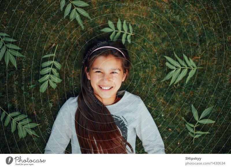Kleines Mädchen, das auf dem Gras und dem Lächeln liegt Kind 1 Mensch 8-13 Jahre Kindheit genießen lachen liegen einfach frei Glück schön klein lustig neu