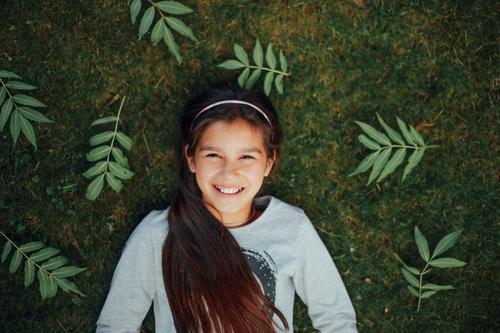 Kleines Mädchen, das auf dem Gras und dem Lächeln liegt Mensch Kind grün schön Sommer Gesicht Auge gelb Liebe lustig Glück lachen klein Schule liegen
