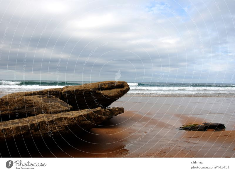 Fels in der Brandung Meer Strand Wolken Stein Küste See Wetter Felsen nass verfallen Fußspur feucht verwittert schlechtes Wetter Spuren