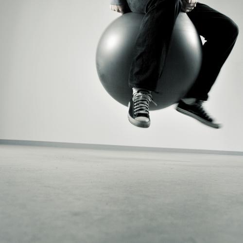 hop hüpfen springen Sprungbein Gummi Turnen Aktion Spielen Gesundheit Hochsprung Luft rund grau schwarz weiß Mann Mensch Bewegung Raum Muskulatur