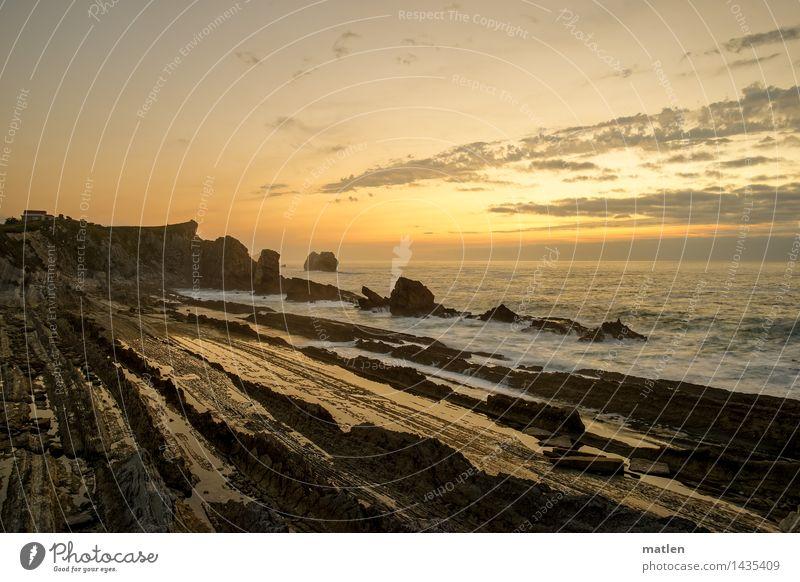 lateral Natur Landschaft Himmel Wolken Horizont Sonnenaufgang Sonnenuntergang Klima Wetter Schönes Wetter Felsen Schlucht Wellen Küste Riff Meer blau braun gold