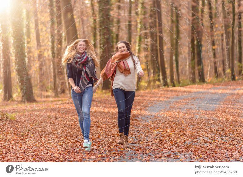 Zwei frohe Frauen, die durch einen Park laufen Lifestyle Freude Gesicht Sonne Erwachsene Freundschaft Hand 2 Mensch 18-30 Jahre Jugendliche Natur Herbst Blatt