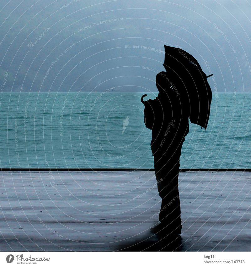 Dancing in the Rain Schweiz See Regen Wasser Meer Regenschirm Wassertropfen schlechtes Wetter Dach Regenjacke Mann Einsamkeit blau grau Himmel 3 Mensch