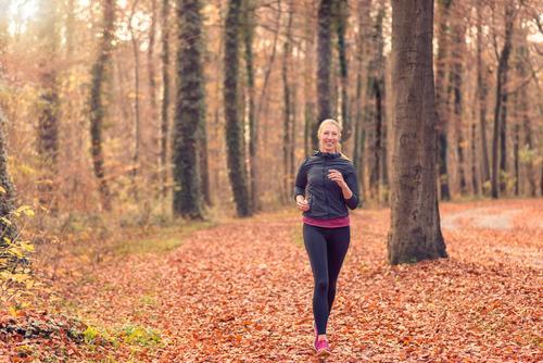Junge Frau des hübschen Sitzes, die im Waldland rüttelt Natur Gesicht Erwachsene Herbst Sport Lifestyle frisch Körper blond Lächeln Fitness Diät Entwurf Läufer