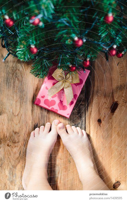 Kind, das unten Geschenk unter Weihnachtsbaum betrachtet Dekoration & Verzierung Mensch Mädchen Fuß Baum Holz Tradition Gast Weihnachten Dezember Etage Feiertag