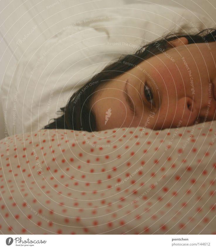 Frau liegt im Bett auf einem gepunkteten    Kopfkissen und schaut   traurig. Müdigkeit, Depression, Krankheit, burn out Gesicht Erholung Schlafzimmer feminin