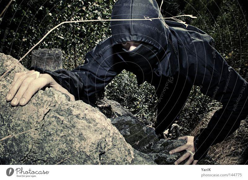 lautloser killer Mann grün schwarz Gesicht dunkel Stein braun orange Felsen Kraft Mund gefährlich Filmindustrie Klettern geheimnisvoll Asien