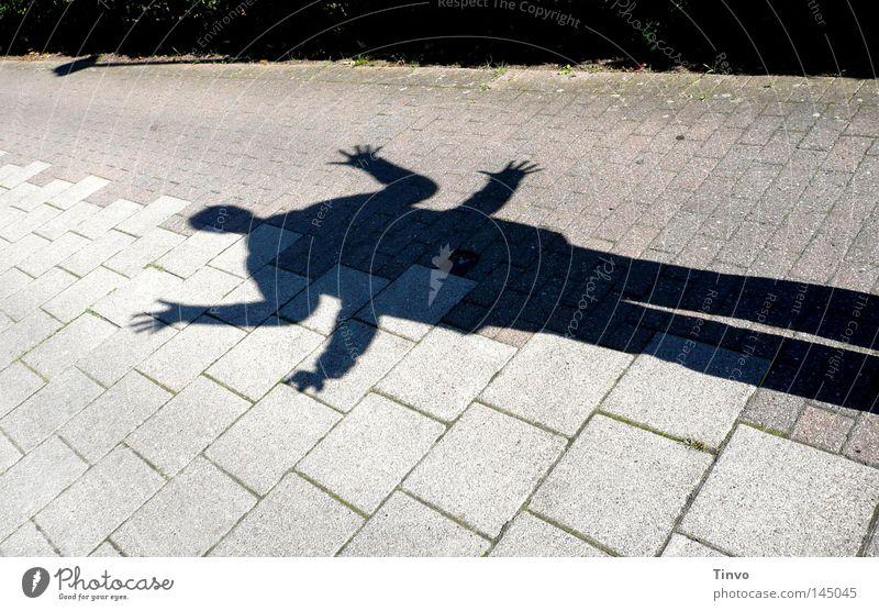Schattenspiel Arme Beine Betonplatte Boden Echsen Finger Phantasie Fuge Bürgersteig Mensch grau Hand hintereinander lang Licht Milbe schwarz Freude Spielen