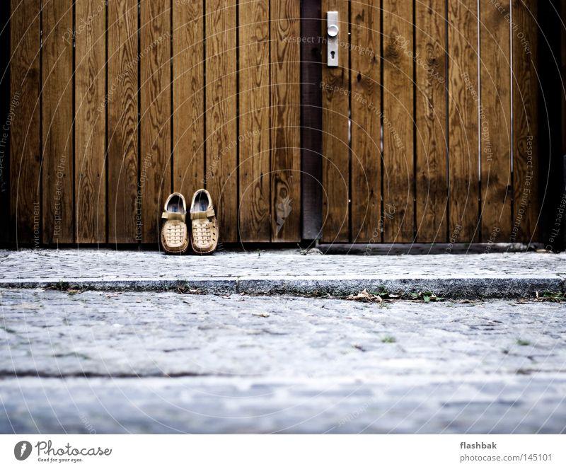 Botten Schuhe Tor Holz Straße Kopfsteinpflaster Pflastersteine Holztor Holztür Außenaufnahme Textfreiraum unten Eingang Eingangstor Eingangstür Bordsteinkante