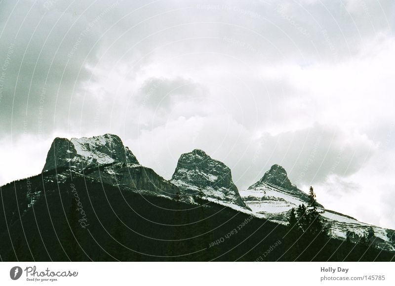 Drei Schwestern Himmel weiß Wolken schwarz dunkel kalt Schnee Berge u. Gebirge hell Regen hoch bedrohlich Gipfel Unwetter Kanada Gegenteil