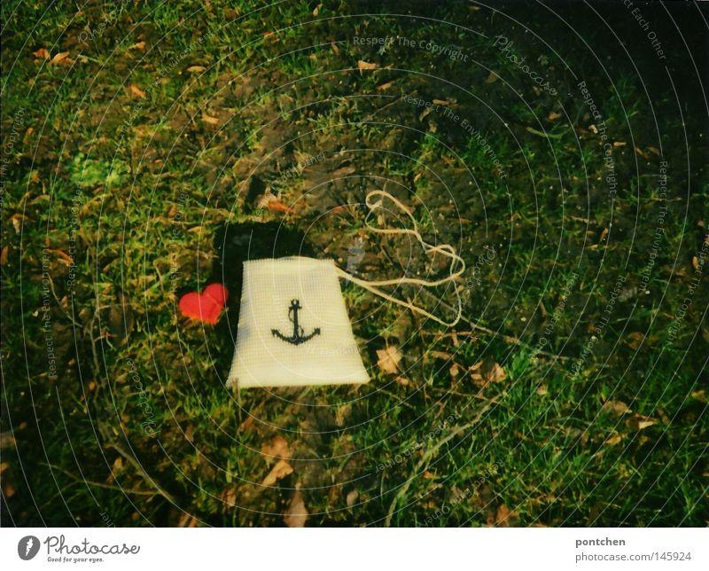 Eine  kleine Tasche bedruckt mit einem Anker liegt im Gras neben einem roten Herz aus Plastik. Liebe und treue. Polaroid Design Natur Erde Herbst Blatt Park