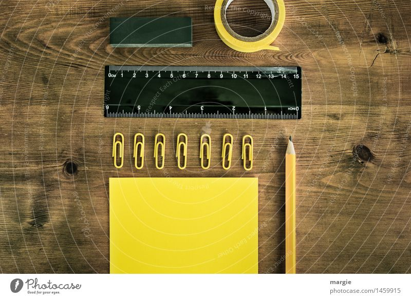 Querformat; gelb schwarze Schreib- Utensilien, Papier, Zettel, Bleistift, Büroklammern, Klebeband, Radiergummi auf einem Holz- Schreibtisch Bildung lernen