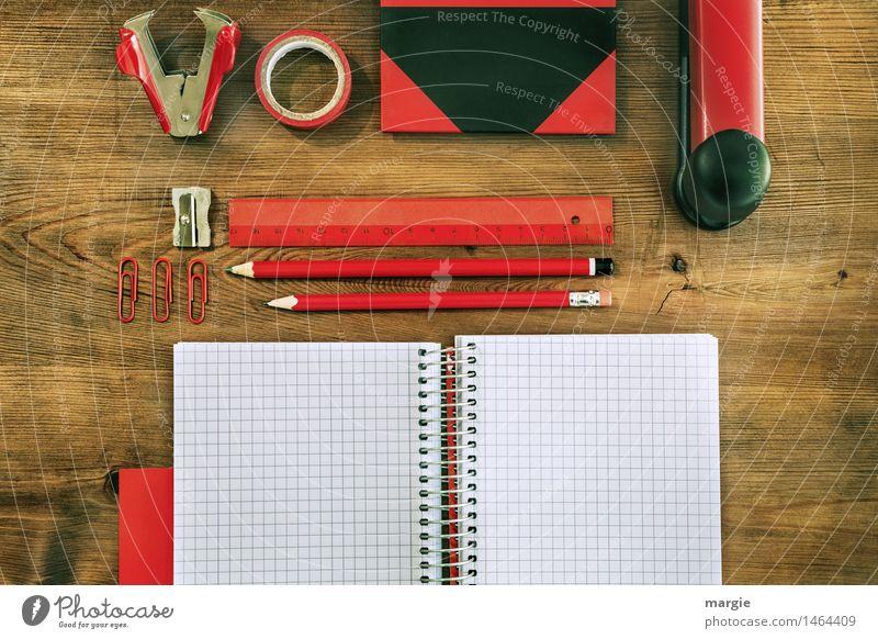 Querformat: Rot- schwarze Schreibtisch Utensilien auf einem Holztisch. Heft, Bleistifte, Lineal, Klebeband, Spitzer, Büroklammern, Buch, Hefter, Klammeraffe