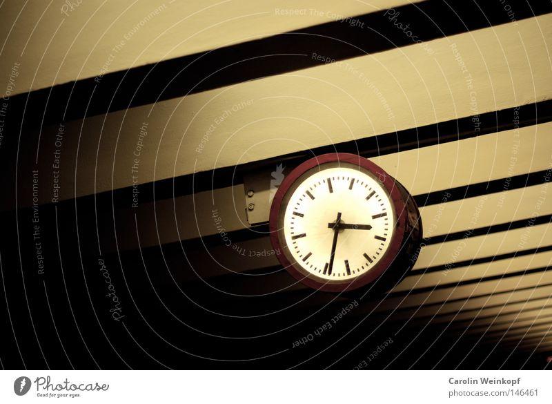 Tick Tack. Uhr rot gelb Licht Bahnhof trashig Decke Balken Uhrenzeiger kurz nach halb vier Schatten warten Zeit U-Bahnstation
