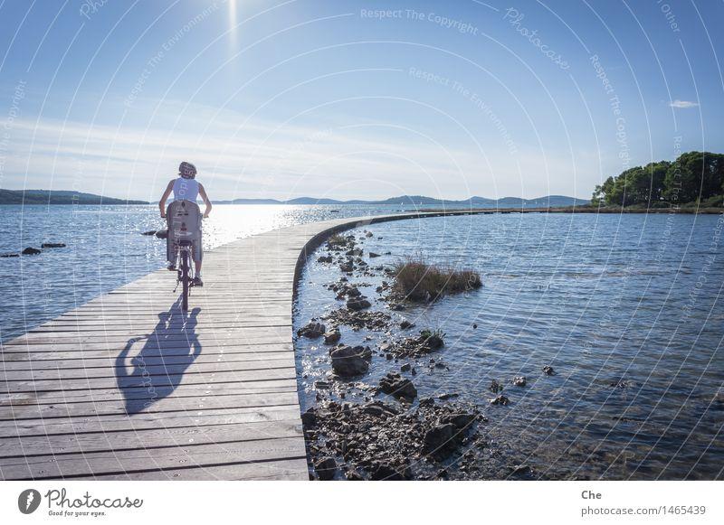 Übers Wasser feminin 1 Mensch 18-30 Jahre Jugendliche Erwachsene fahren Fahrrad Kindersitz Familie & Verwandtschaft Anlegestelle See Meer Biken Fahrradtour