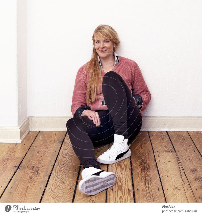 Ganzkörperportrait einer jungen Frau in Sneakers, die auf einem Dielenboden sitzt Wohnung Raum Junge Frau Jugendliche Körper 18-30 Jahre Erwachsene Pullover