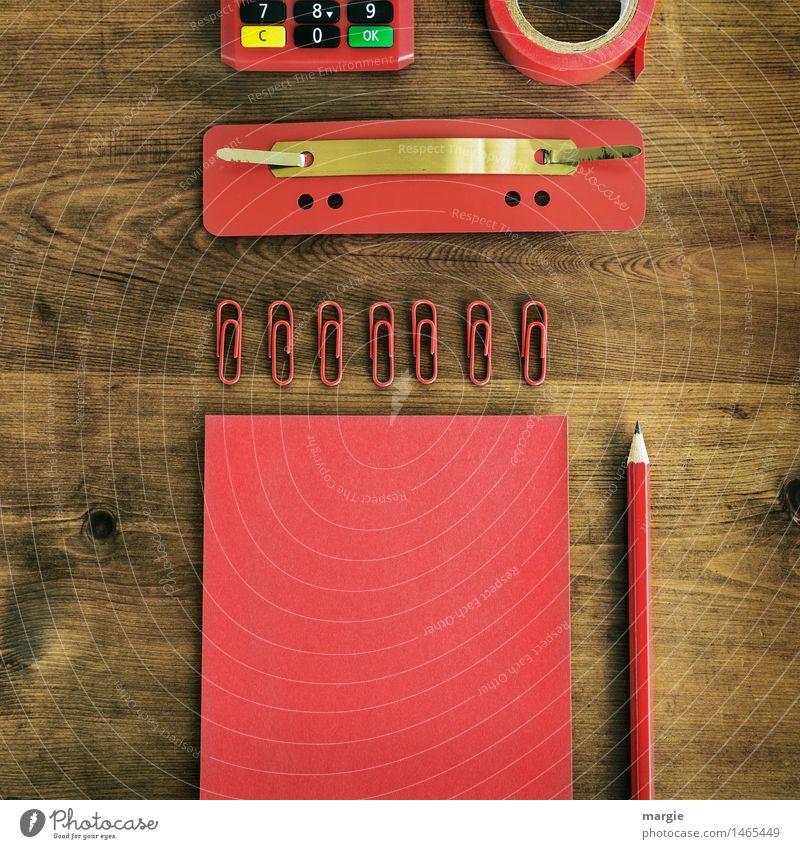 Im Q- Format: rote Schreib- Utensilien, Papier, Zettel, Bleistift, Büroklammern, Heftlasche, Klebeband, Rechner auf einen Holz- Schreibtisch Berufsausbildung