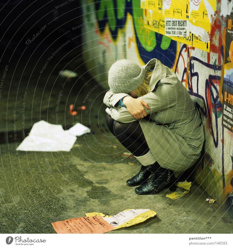 Sara Jane Frau Trauer sitzen hocken Mantel Strumpfhose Mütze Wollmütze Graffiti Aufschrift Unterführung nass kalt Wand mehrfarbig Verzweiflung Liebeskummer