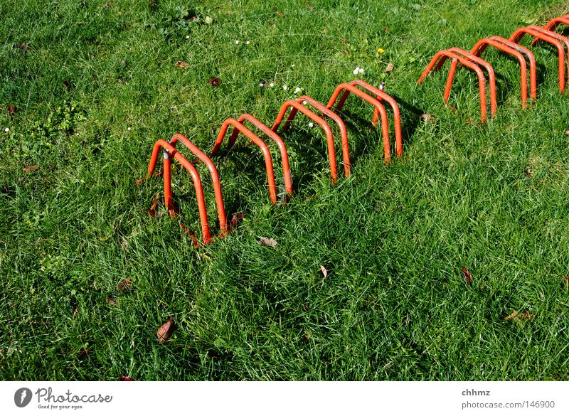 Radständer Fahrradständer Rasen Wiese rot grün diagonal Reihe Ordnung stellen parken Detailaufnahme Spielen Verkehr mehrere Örtlichkeit