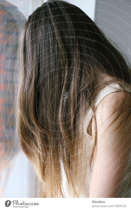 Seitliches Portrait einer jungen, dunkelblonden Frau, die an einer Fensterscheibe lehnt, so dass man nur ihre langen Haare sieht Haare & Frisuren Zufriedenheit