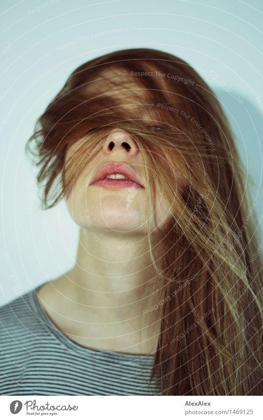 Portrait eine dunkelblonden, langhaarigen Frau, die durch ihre Haare im Gesicht in die Kamera schaut Lifestyle Stil schön Junge Frau Jugendliche