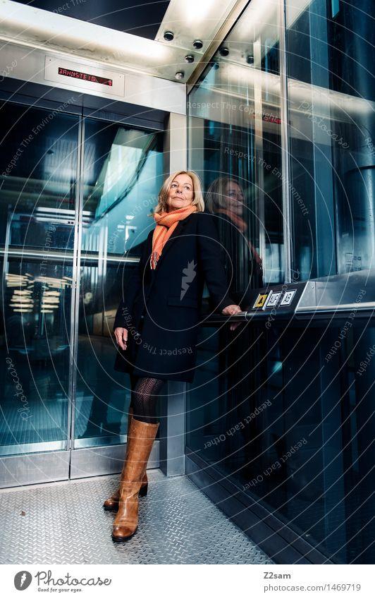 Es muss wieder aufwärts gehen Lifestyle elegant Stil feminin Junge Frau Jugendliche 45-60 Jahre Erwachsene Fahrstuhl Rock Mantel Stiefel blond sprechen Lächeln