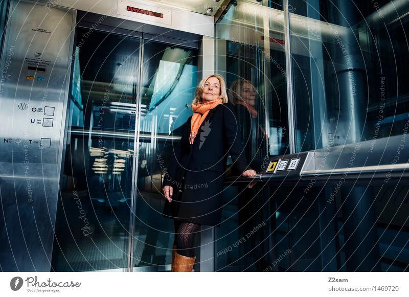 Traudl Lifestyle elegant Stil Frau Erwachsene Weiblicher Senior 45-60 Jahre Stadtzentrum Fahrstuhl Mode Mantel Schal Stiefel blond Lächeln stehen Coolness
