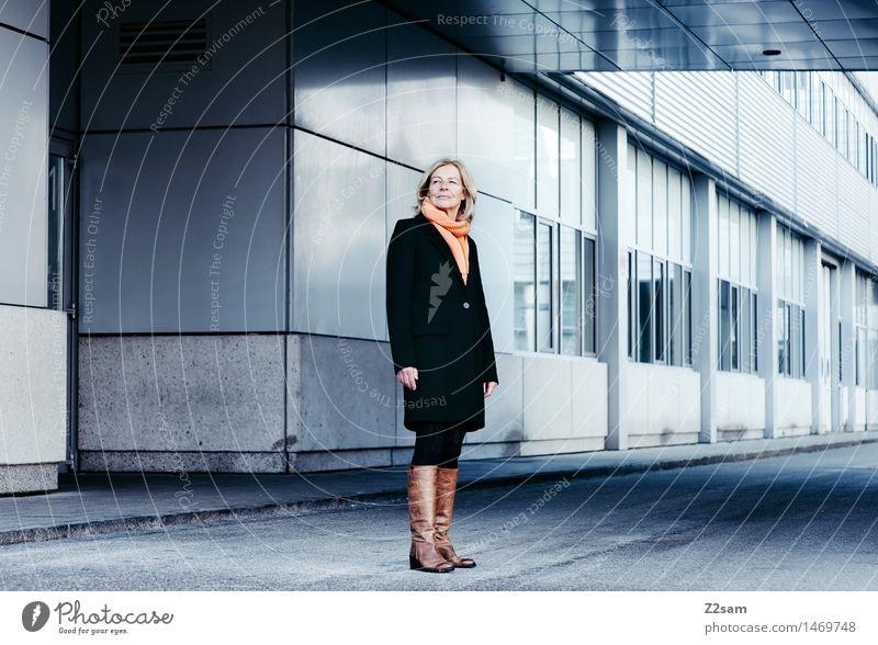 Schulterblick feminin Weiblicher Senior Frau 1 Mensch 45-60 Jahre Erwachsene Bauwerk Gebäude Architektur Mantel Schal Stiefel blond Blick stehen warten Coolness