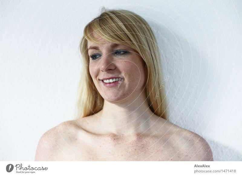 Portrait einer jungen, sommersprossigen Frau vor einer weißen Wand - ein lizenzfreies Stock Foto