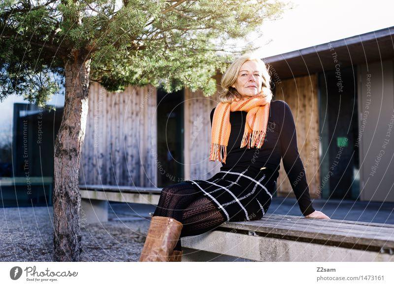 50 Jährige sitzt auf der Bank in der Sonne Lifestyle elegant Stil feminin Frau Erwachsene 60 und älter Senior Herbst Schönes Wetter Baum Stadt Haus Mode Rock