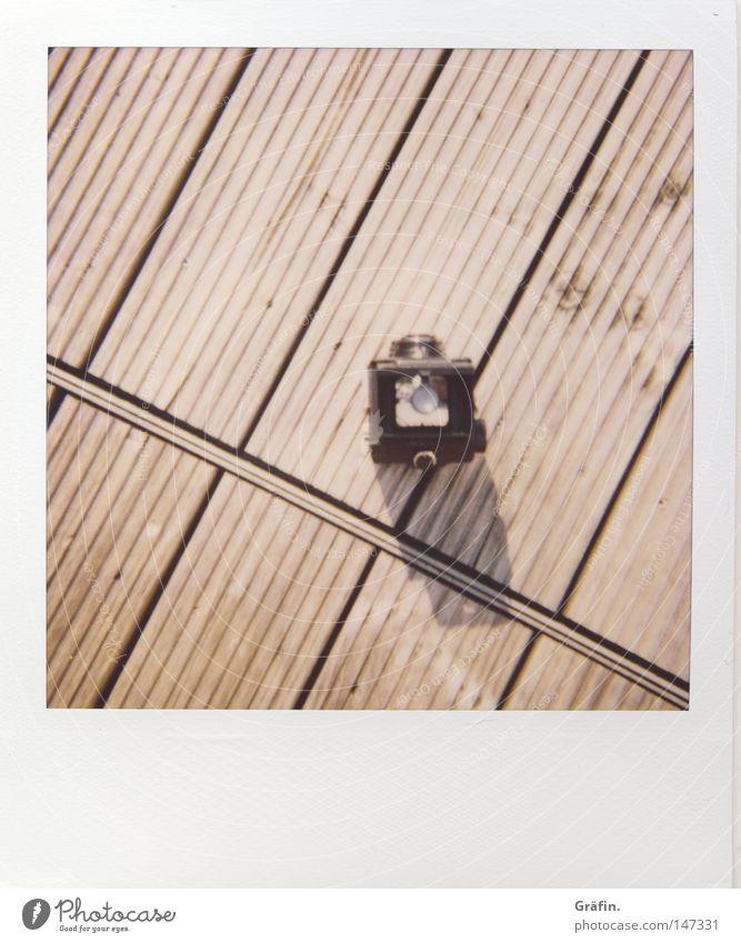 Lubitel Polaroid Geschwindigkeit teuer Lomografie Fotokamera Fotografieren Balkon Holzfußboden Bodenbelag Holzbrett Sommer Schatten minimalistisch Furche quer