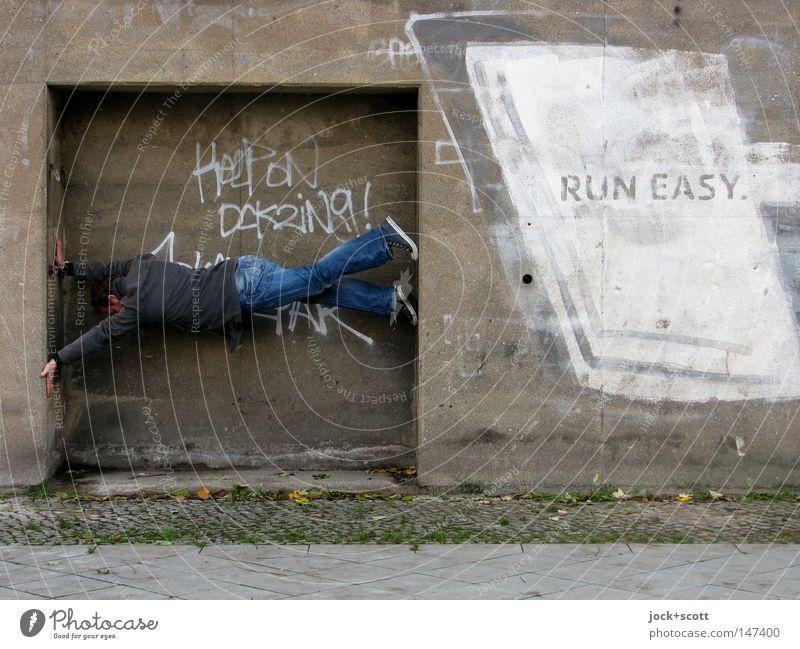 Bln08_Don't ask! Run Easy Mensch Mann Erwachsene Graffiti Wand Mauer grau Schriftzeichen Beton einfach Körperhaltung festhalten Ziel sportlich Jeanshose