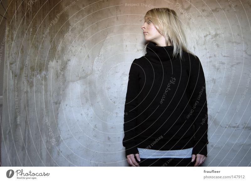 Seitenblick Frau dunkel Wohnzimmer Raum Europäer Jugendliche Wand Mauer scheckig dreckig nass grau braun dunkelgrau Riss Pullover schwarz Kragen Hose blond lang