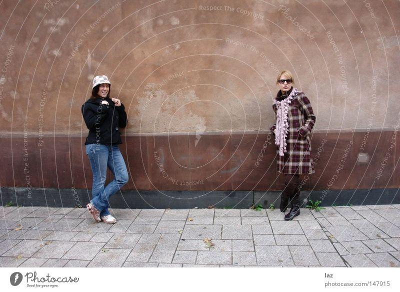 Two Girls Frau Jugendliche alt Freude Winter Wand grau Mauer Freundschaft Jeanshose Mütze Jeansstoff eng Flucht Riss