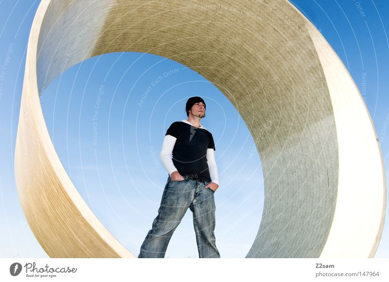 mittelpunkt Mensch Mann Himmel blau Stil Denken Beton modern Coolness Jeanshose rund stehen Baustelle Mütze Material