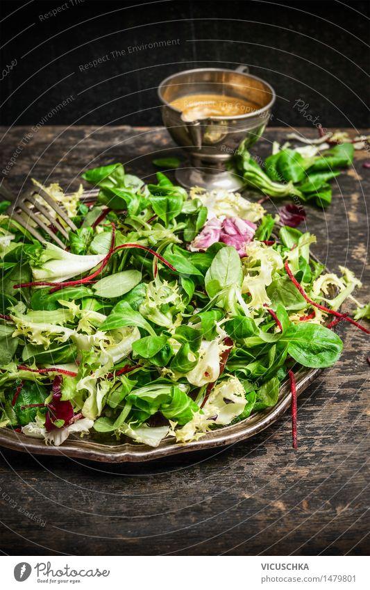 Gesunde grüner Salat mit Dressing auf dunklem Hintergrund Lebensmittel Salatbeilage Ernährung Mittagessen Bioprodukte Vegetarische Ernährung Diät