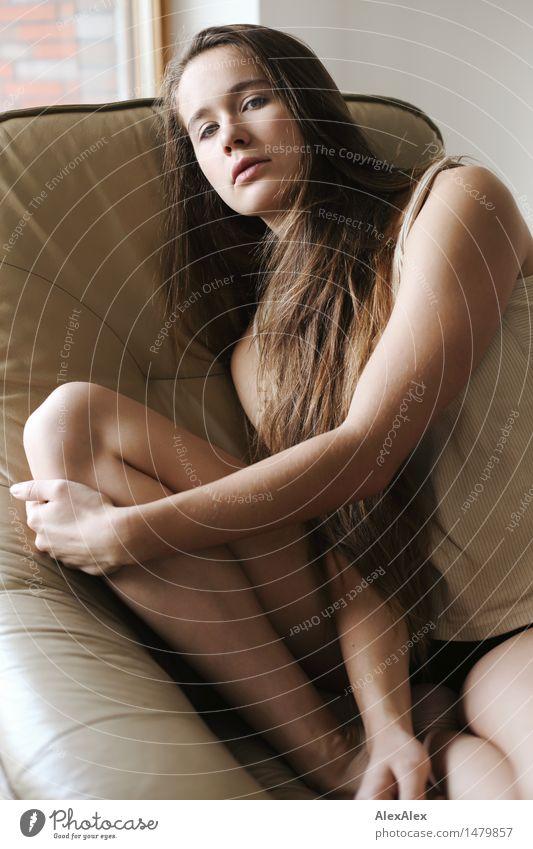Junge, schlanke, sportliche Frau in Unterwäsche sitzt seitlich auf einem Sessel und schaut in die Kamera Stil schön Wohlgefühl Erholung Raum Junge Frau