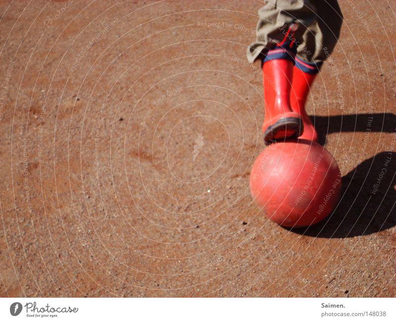 Fußball aus Leidenschaft rot Freude Spielen Kraft dreckig Energiewirtschaft Armut Ball Falte Hose Stiefel grinsen Staub Fußballplatz Gummistiefel
