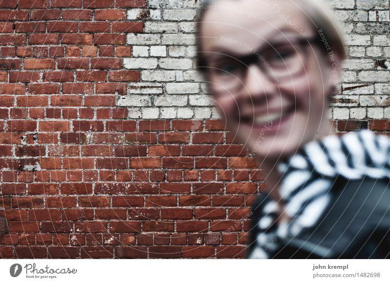 una.fotobombolina feminin Junge Frau Jugendliche Gesicht 1 Mensch 13-18 Jahre 18-30 Jahre Erwachsene Mauer Wand Backsteinwand Brille lachen springen Coolness