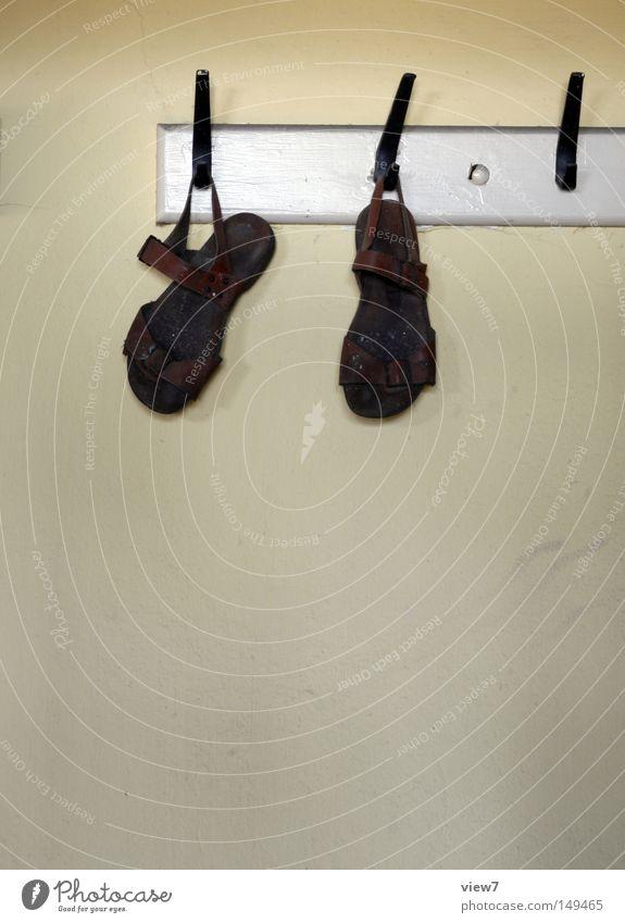 Sandalen Schuhe laufen aufgehen aufhängen Kleiderbügel Bekleidung Kleiderständer Flur Detailaufnahme Lederband Schnalle Schuhsohle Fuß Wand Tapete Putz obskur
