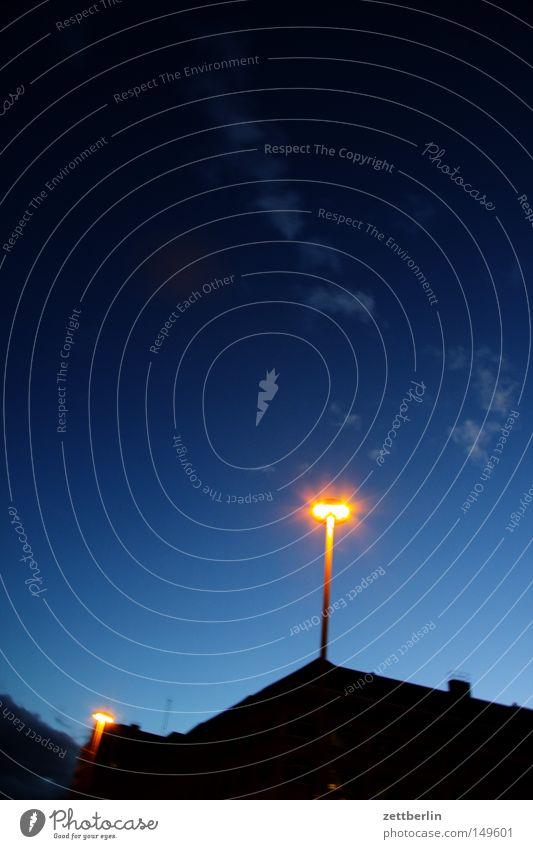 Nacht Lampe Laterne Beleuchtung Straßenbeleuchtung Licht Himmel Nachthimmel blau dunkel Wolken Haus Dachgiebel Stadt Detailaufnahme Langzeitbelichtung