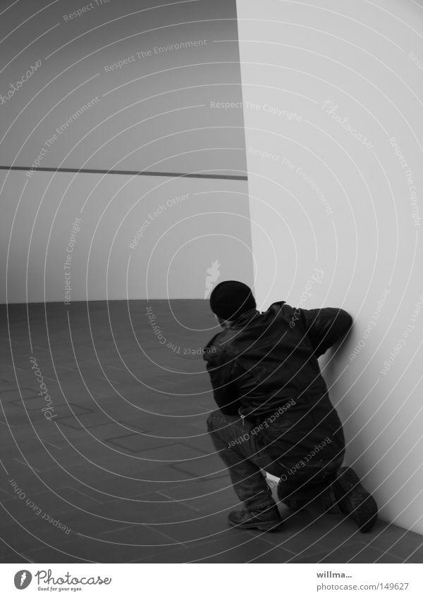 Der Stalker Mann hocken knien lauern warten Spanner gefährlich Erwartung geheimnisvoll Kontrolle Wand Spannung Voyeurismus abstützen verstecken Suche Ecke