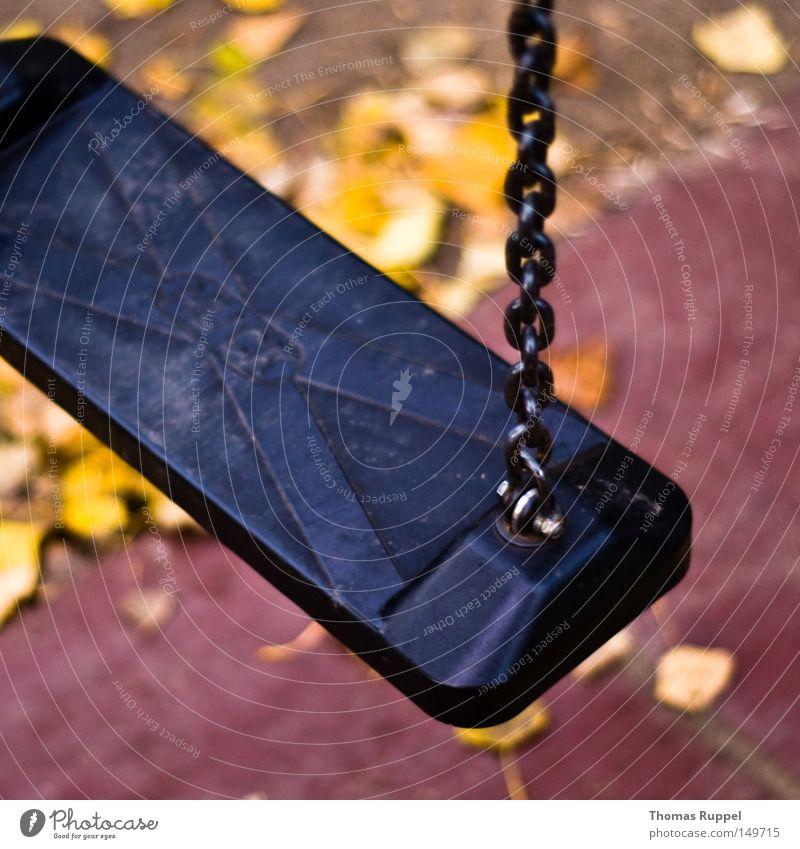 Stillstand auf dem Spielplatz Schaukel dunkel grau schwarz Menschenleer Kette Blatt Unschärfe gelb Herbst Spielzeug Kindheit Spielen Freude Außenaufnahme