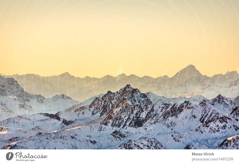 Gelber Himmel in den Bergen Umwelt Natur Landschaft Wolkenloser Himmel Sonne Sonnenaufgang Sonnenuntergang Sonnenlicht Winter Schnee Hügel Felsen Alpen