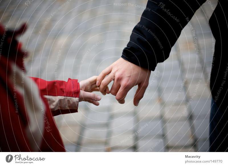 Nicht loslassen Vertrauen Freundschaft Kind Mann Frau Partnerschaft Hand Finger greifen Kopfsteinpflaster Anorak berühren Verbindung rot grau klein Jacke kalt