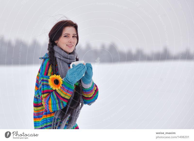 Junge Frau in einer Strickjacke auf einem Winterweg Kaffee Tee Becher Glück schön Ferien & Urlaub & Reisen Schnee wandern Mensch Jugendliche Erwachsene Körper