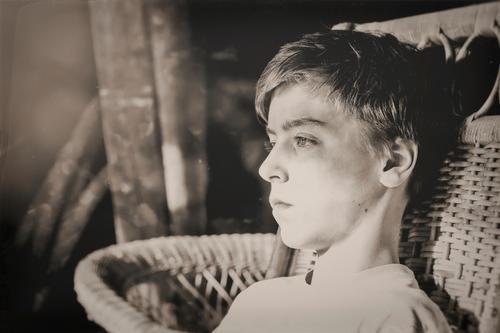 Schwarz Weiß Bild eines Jugendlichen in einem Korbsessel Lifestyle Stil Design schön Sinnesorgane Erholung ruhig Dachboden Mensch maskulin Junger Mann Kopf 1