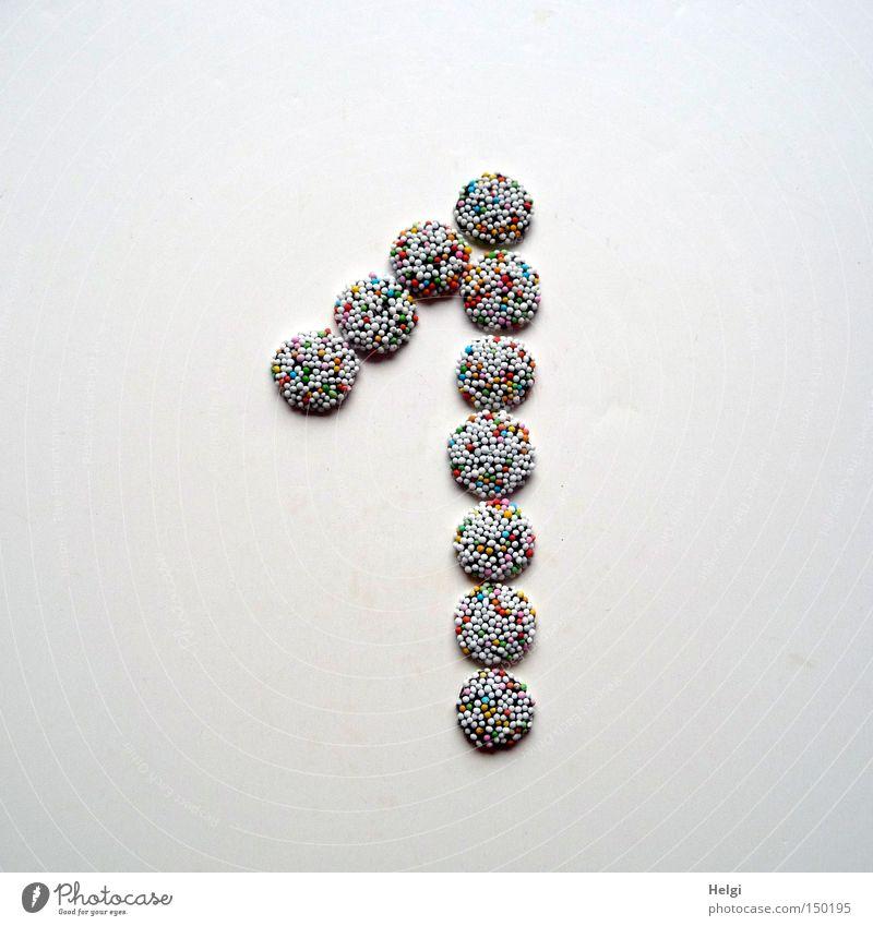 Zahl 1 aus kleinen Schokoladenbonbons mit bunten Zuckerstreuseln auf weißem Hintergrund Ziffern & Zahlen Adventskalender Tür Bonbon Süßwaren Streusel