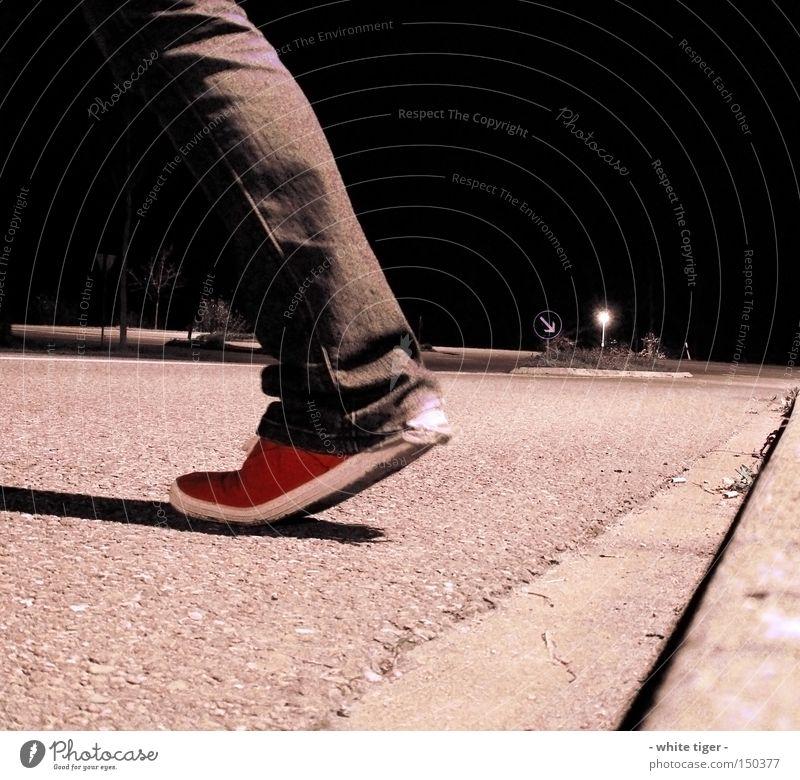 nightly walking Bekleidung Hose Jeanshose Schuhe Schilder & Markierungen rot Straßenbelag Asphalt Bordsteinkante Verkehrsinsel Farbfoto Außenaufnahme Nacht
